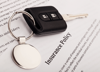 a sheet of paper that reads insurance policy with a set of car keys on top of it