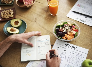 hands writing in a health journal on a table surrounded by healthy foods